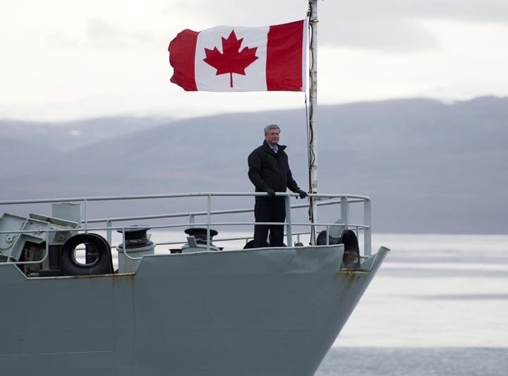 Prime Minister Stephen Harper stands on the bow of the HMCS Kingston as it sails in the Navy Board Inlet Sunday August 24, 2014.