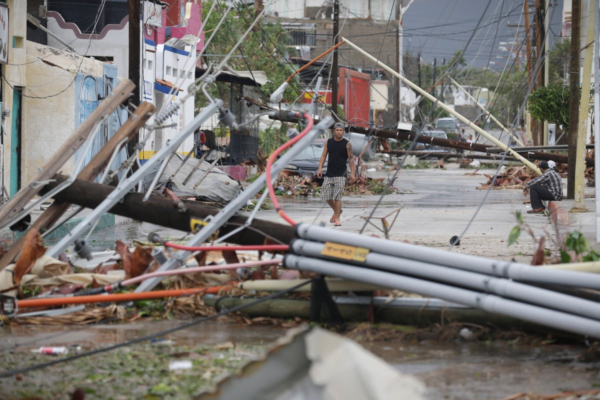 A man walks on a street where most power lines and light posts have been knocked down by Hurricane Odile, in Los Cabos, Mexico, Monday, Sept. 15, 2014. The storm, which made landfall near Cabo San Lucas the previous night as a powerful Category 3 hurricane, toppled trees, power poles and road signs along the main highway, which at one point was swamped by rushing floodwaters. (AP Photo/Victor R. Caivano).