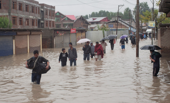 Kashmiris walk through a flooded area to a safer place on September 04, 2014 in Srinagar, the summer capital of Indian administered Kashmir, India.  The floods in the Himalayan region are believed floods to be the worst in decades, killing 15 people and and affecting some 50,000 families.