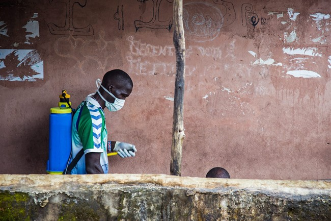 A health worker, left, sprays disinfectant around the area where a man, right, suspected of suffering from the Ebola virus, sits with a part of his head visible, before loading him into an ambulance in Freetown, Sierra Leone, Wednesday, Sept. 24, 2014.