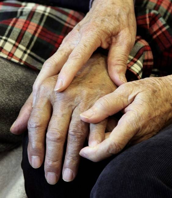 A care giver holds the hand of her husband, an Alzheimer's patient.