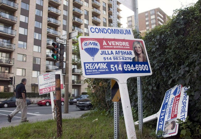 In this file photo, a real estate sign stands in front of a condo in Montreal. The number of condo sales across the region surged 23 per cent from last year to 1,137 in November. Thursday, Dec. 7, 2017.