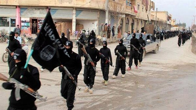 """This file image posted on a militant website on Tuesday, Jan. 14, 2014, shows fighters from the al-Qaida linked so-called Islamic State, marching in Raqqa, Syria. Canadians who abandoned this nation for IS and similar organizations are officially dubbed """"terrorist travellers"""" and some 200 have reportedly returned to face absolutely no legal consequences."""