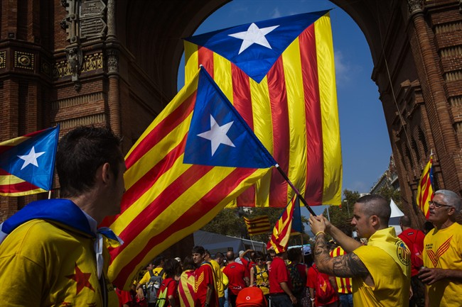 """People wave """"estelada"""" flags symbolizing Catalonia's independence in Barcelona, Spain, Thursday, Sept. 11, 2014. The region has set an Oct. 1, 2017 referendum vote to decide whether to split from Spain."""