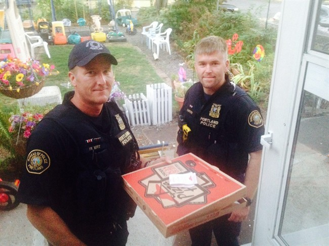 In this photo taken Sept. 1, 2014, and provided by Steve Huckins, Portland police officers Michael Filbert, left, and Royce Curtiss, right, pose after completing a pizza delivery to the Huckins home after a Pizza Hut delivery driver was hurt in a crash in Portland, Ore. (AP Photo/Steve Huckins).