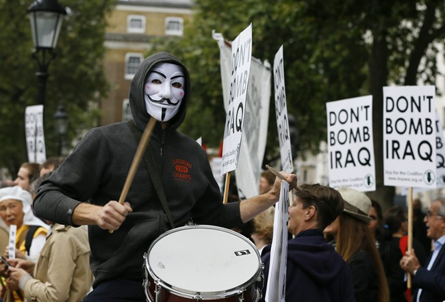 A demonstrator bangs a drum at an anti-war demonstration near Downing Street in London, Thursday, Sept. 25, 2014. The British prime minister said late Wednesday he will ask Parliament to approve joining international airstrikes against the Islamic State group in Iraq. David Cameron announced the move in his address to the U.N. General Assembly. (AP Photo/Kirsty Wigglesworth).