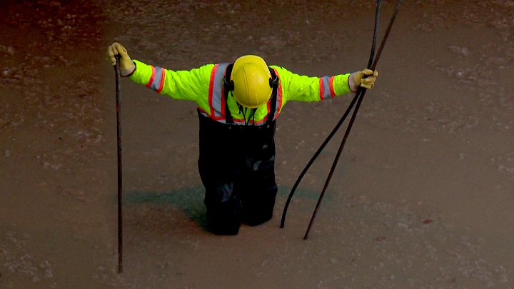 A City of Winnipeg worker investigating a water main break.