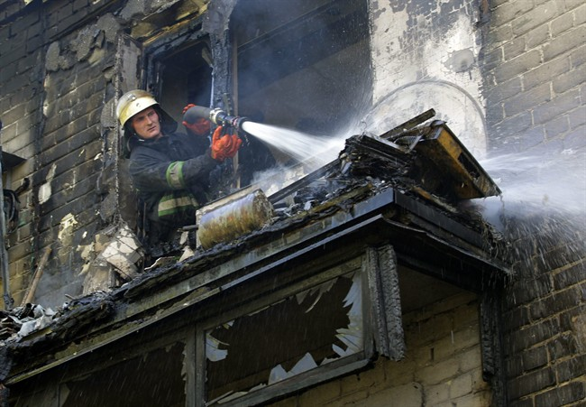 A firefighter sprays water at damaged apartment building after shelling in the town of Donetsk, Wednesday, Sept. 17, 2014.