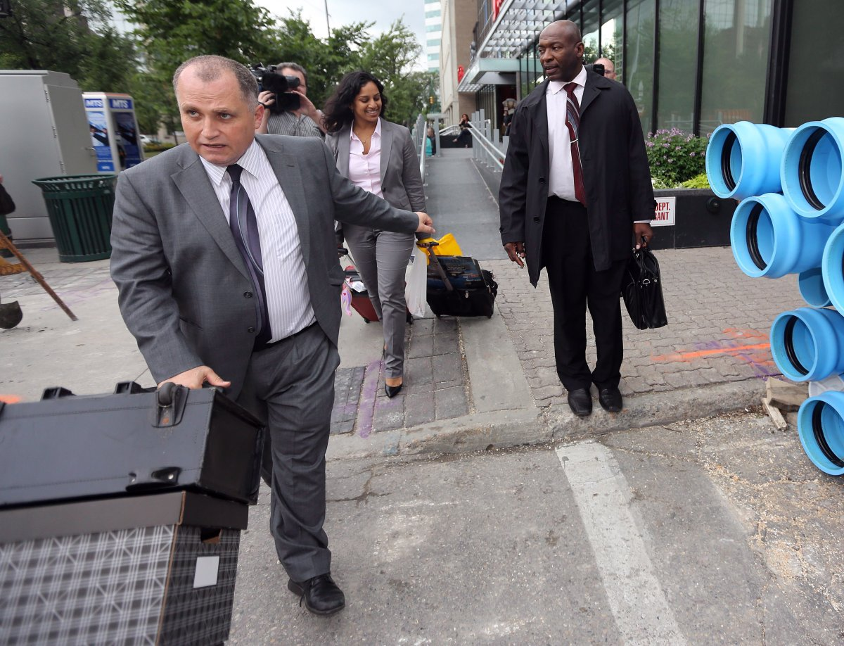 Toronto based attorney, Rocco Galati, left, leads his client, Alex Chapman, out of the Federal Court Building in Winnipeg.