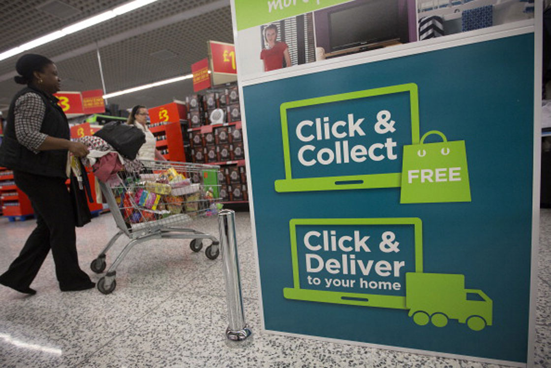 A customer pushes a shopping cart past a 'click and collect' pick-up point inside a Walmart-owned store in the United Kingdom. Some grocers have begun trialing the same service in Canada.