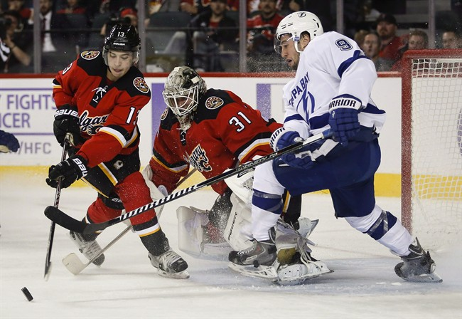 Tampa Bay Lightning Tyler Johnson, right, fights for the puck as Calgary Flames Johnny Gaudreau, left, swats it away while goalie Karri Ramo, from Finland, looks on during second period NHL hockey action in Calgary, Tuesday, Oct. 21, 2014.