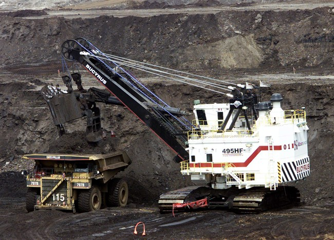 A hydraulic shovel loads a heavy hauler at an oilsands mine north of Fort McMurray, Alta. on June 19, 2003.