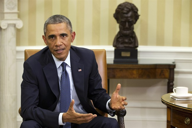 President Barack Obama speaks to the media about the government's Ebola response, in the Oval Office of the White House Thursday, Oct. 16, 2014, in Washington.