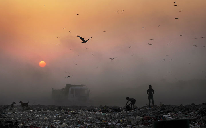 A thick blanket of smoke is seen against the setting sun as young ragpickers search for reusable material at a garbage dump in New Delhi, India, Friday, Oct. 17, 2014. The WHO says that 1.7 million children die every year due to polluted environments.