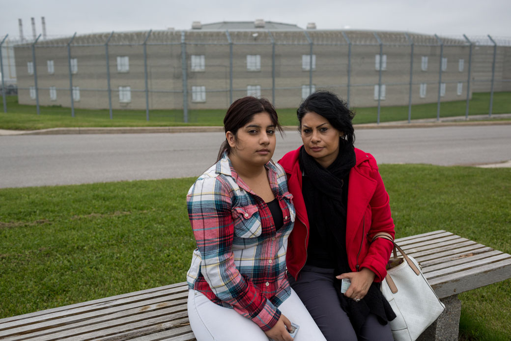 Pam Shiraldini and Melika Mojarrab, 15, sit in front of the Lindsay jail after visting Masoud Hajivand, held in immigration detention there.