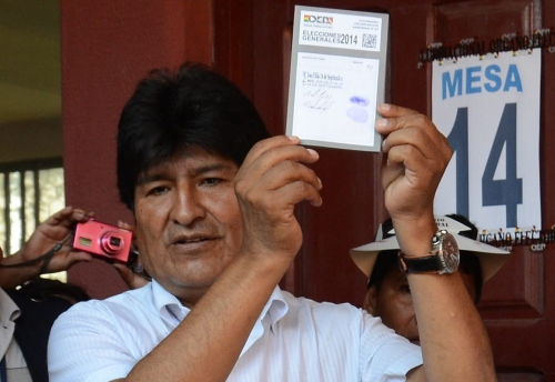 Bolivian President and candidate to the reelection for the Movimiento Al Socialismo (MAS) party Evo Morales (L) shows his ballot prior to vote in Villa 14, Chapare, Bolivia on October 12, 2014.