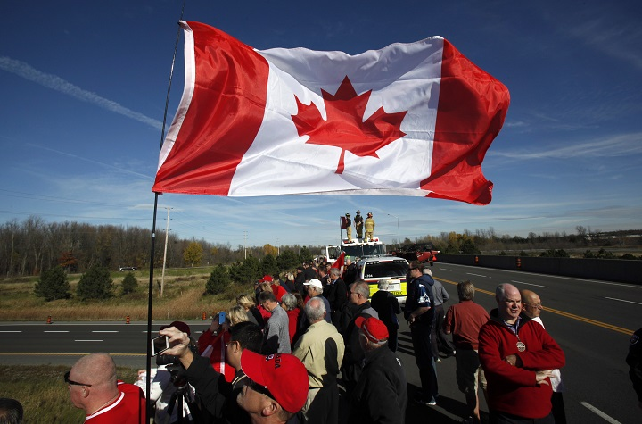 Crowds wave Canadian flags on an overpass at the Veterans Memorial Highway waiting for a procession transporting the body of Cpl. Nathan Cirillo to pass by in Ottawa on Friday, October 24, 2014.