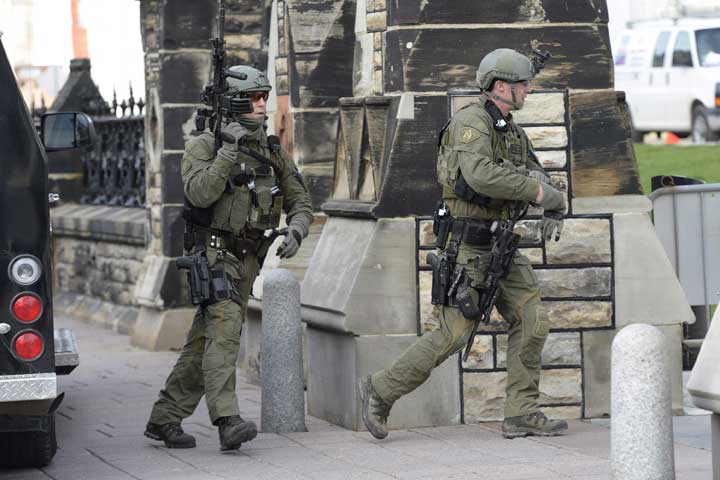 RCMP intervention team members walk past a gate on Parliament hill in Ottawa Wednesday Oct.22, 2014.
