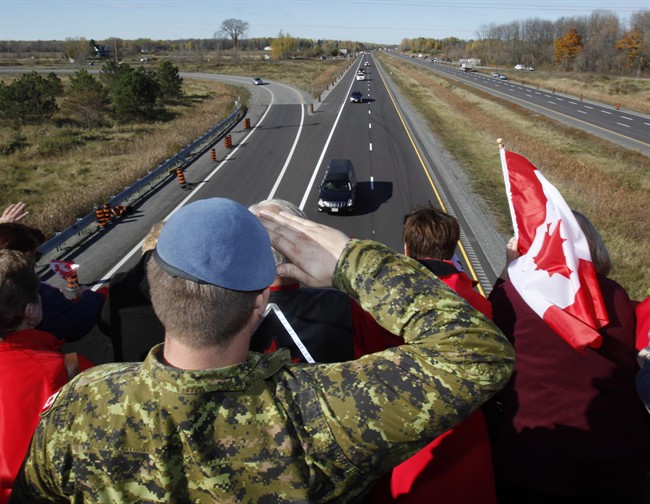 A Canadian Soldier salutes the hearse carrying the body of Cpl. Nathan Cirillo on the Veterans Memorial Highway in Ottawa on Friday, October 24, 2014.
