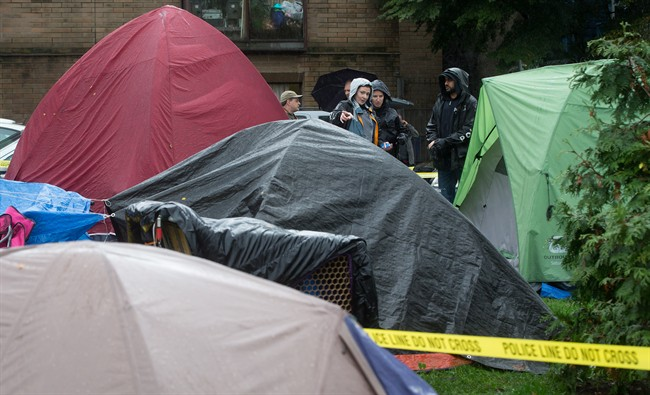 Police officers talk at the scene where a man was found dead at a tent city at Oppenheimer Park in the Downtown Eastside of Vancouver, B.C., on Wednesday October 15, 2014. A B.C. Supreme Court judge granted a court order last week allowing the city to clear tents and campers from the park after 10 p.m. Wednesday. The encampment began in July when people set up tents to bring attention to affordable housing in the city. THE CANADIAN PRESS/Darryl Dyck.