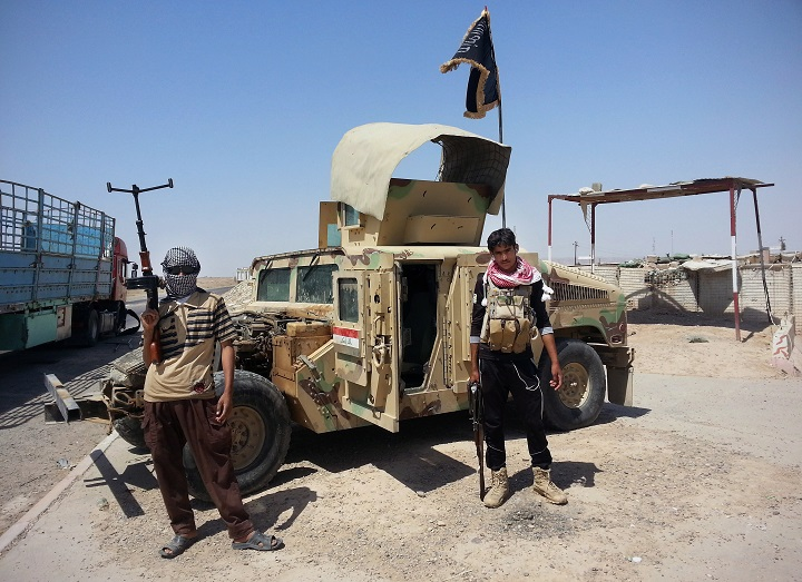 Islamic State militants stand with a captured Iraqi Army Humvee at a checkpoint outside Beiji refinery, some 250 kilometers north of Baghdad, Iraq.