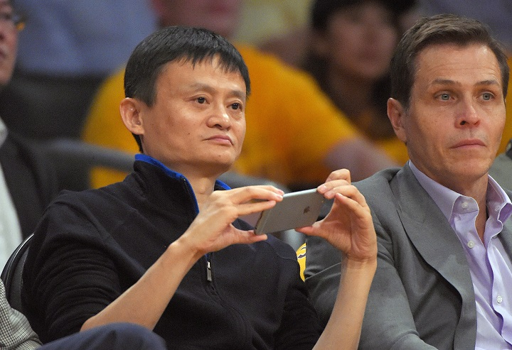 Jack Ma, left, executive chairman of Alibaba Group, watches the Los Angeles Lakers play the Houston Rockets during the first half of an NBA basketball game, Tuesday, Oct. 28, 2014, in Los Angeles.