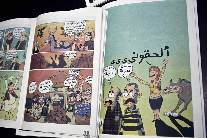 This Wednesday, Nov. 12, 2014 photo shows works by comic book artist Hagrassy, from Shakmagia magazine, at a coffee shop in Cairo. Cartoons and political satire go back more than 100 years in Egypt, and are a staple in newspapers that have often lampooned social mores and officials in public office. But a new generation of young comic artists is finding alternative space to express what is often a hard sell in mainstream media.