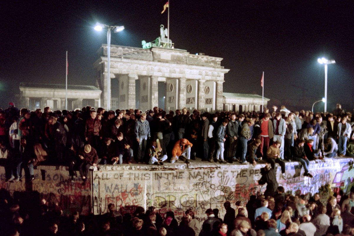 People dance on top of the Berlin Wall