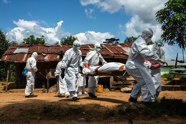 A body is carried to the back of a pickup truck by a county health burial team on Friday November 7, 2014 in Voinjama, Liberia.