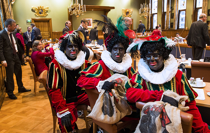 (L-R) Dutch right wing PVV State members Ton van Kesteren, Matthijs Jansen and Dennis Ram dressed as Black Pete, the jolly sidekick of the Dutch Saint Nicholas, attend a meeting in the Province House in Groningen, The Netherlands, on November 5, 2014.