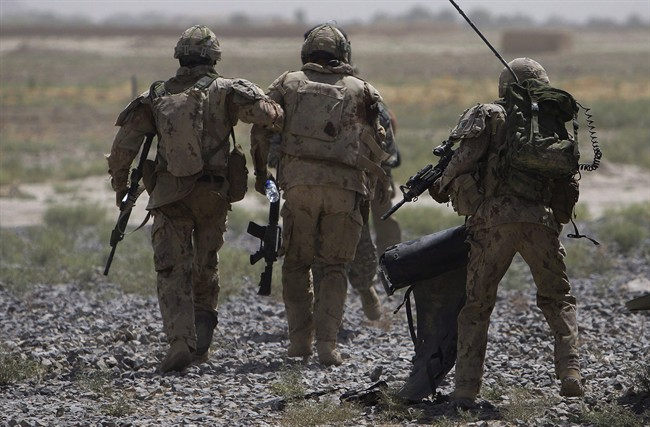 Canadian soldiers help a comrade, center, getting on a helicopter after he was injured in an IED blast during a patrol outside Salavat, Afghanistan, Monday, June 7, 2010.