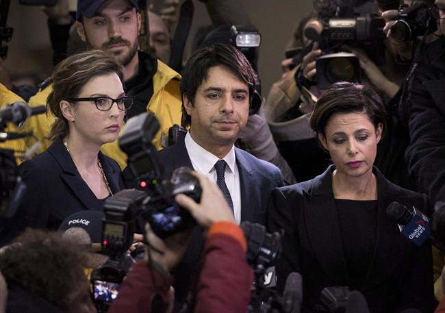 Jian Ghomeshi makes his way through a mob of media with his lawyer Marie Henein (right) at a Toronto court Wednesday, November 26, 2014.
