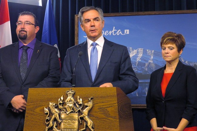 Alberta Premier Jim Prentice (centre) announces Monday, Nov.24, 2014 at legislature in Edmonton that opposition Wildrose members Ian Donovan, left, and Kerry Towle, right, have crossed the floor to join his Progressive Conservative caucus.