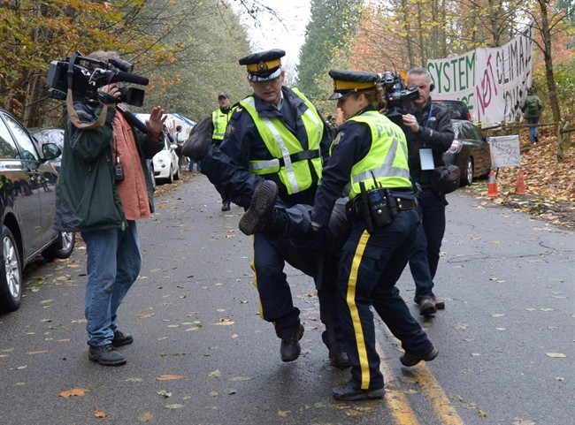 RCMP officers remove a protestor at an anti-pipeline demonstration in Burnaby, B.C., on Thursday, Nov. 20, 2014.