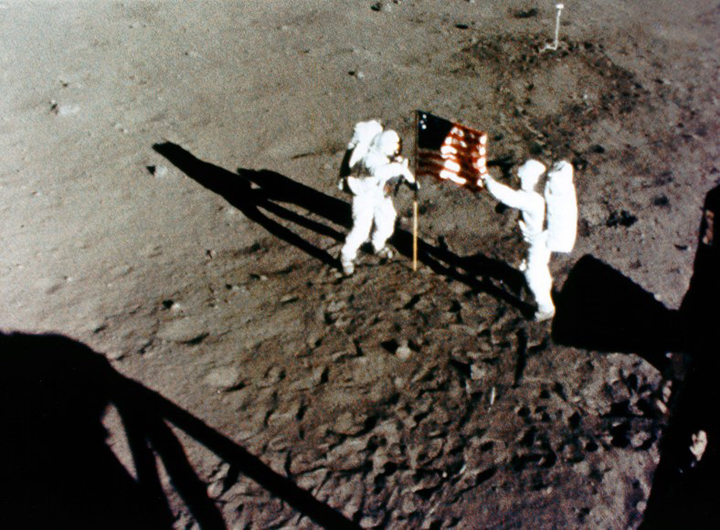 A camera mounted in the Lunar Module window photographs Neil Armstrong (left) and Buzz Aldrin (right) deploying the U.S. Flag on July 20, 1969.