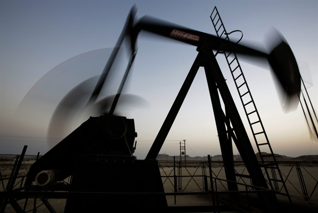 In this Oct. 14, 2014 file photo, an oil pump works at sunset in the desert oil fields of Sakhir, Bahrain.