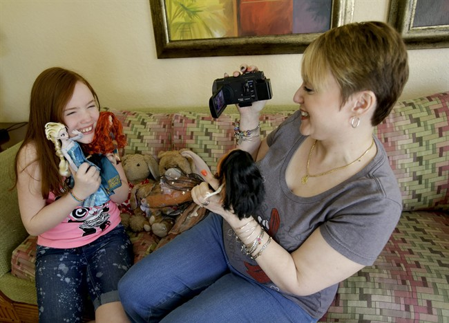 "Gracie Hunter, left, and her Mom, Melissa make a video for a doll review while on vacation in Kissimmee, Fla. The mother-daughter duo, stars of the ""Mommy and Gracie"" YouTube show, review dolls for kids."
