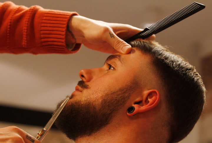 In this Nov. 13, 2014, photo, Salvador Chanza, 31, a master barber from Spain, who also calls himself Lord Jack Knife, trims the beard of Jakub Marczewski, with scissors at the Barberian Academy & Barber Shop in Warsaw, Poland. Chanza was sharing his expertise at the shop, which opened last month in Warsaw as beards are enjoying a comeback in the Polish capital.