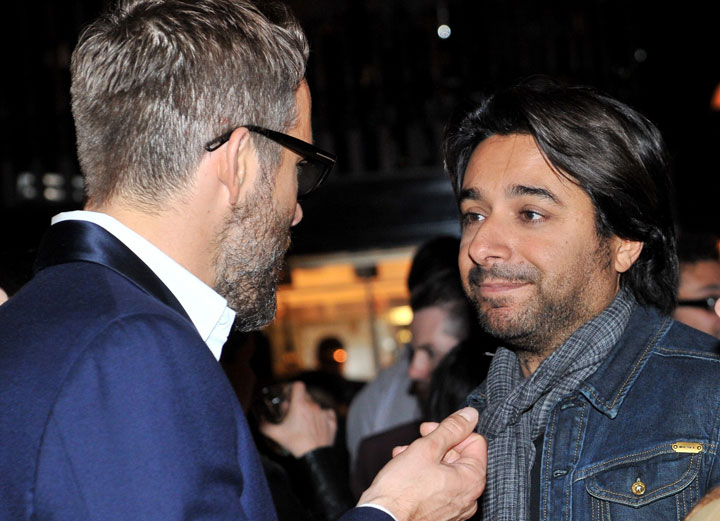 Jian Ghomeshi, right, talks to Ryan Reynolds at a party during the 2014 Toronto International Film Festival.