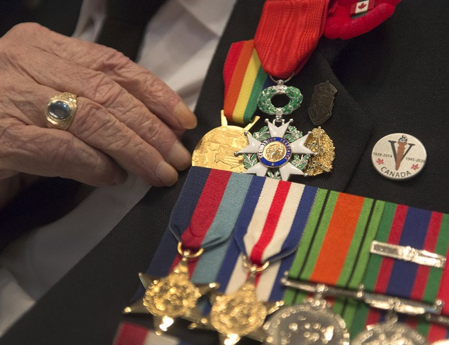 A veteran adjusts his medals in this 2014 file photo. Officials are hoping the province's new pilot project can help support veterans who end up in contact with the justice system.