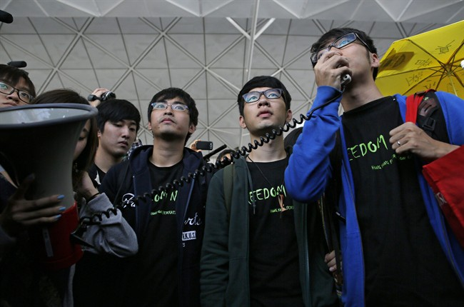 Hong Kong Federation of Students leader Alex Chow, left, committee members Nathan Law, centre, and Eason Chung speak to supporters before attempting to travel to Beijing, at Hong Kong International Airport Saturday, Nov. 15, 2014.