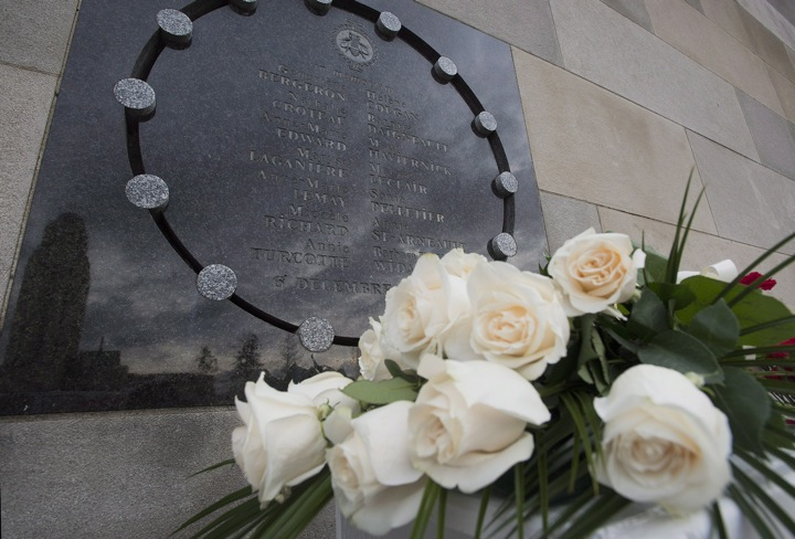 Flowers sit next to a plaque at the École Polytechnique in Montreal.