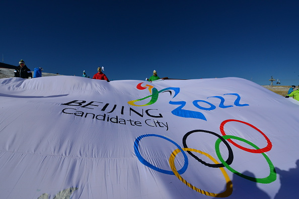 People demonstrate a flag of Beijing applying for hosting the 2022 Winter Olympic Games at Chongli County Ski Resort on November 22, 2014 in Chongli County, Heibei Province of China.