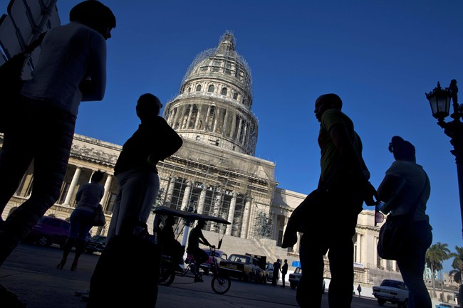 People line up to take the bus outside the Capitolio in Havana, Cuba, Thursday, Dec. 18, 2014.