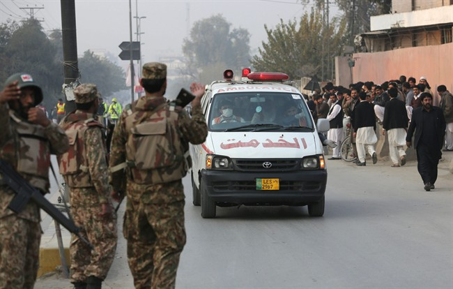 Ambulances carry injured people outside a school attacked by the Taliban in Peshawar, Pakistan, Tuesday, Dec. 16, 2014.