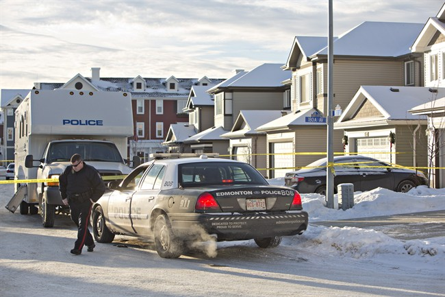 Police investigate the scene where multiple deaths occurred in a north Edmonton home overnight in Edmonton, Alberta on Tuesday, December 30, 2014. THE CANADIAN PRESS/Jason Franson.