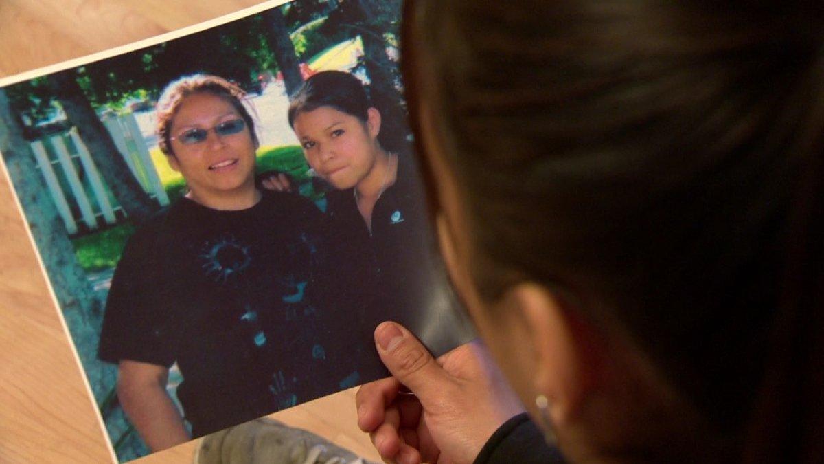 Tia Ledesma looks at a photograph of her mother Cherry Ledesma.