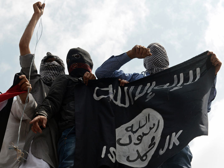 Demonstrators hold up a flag of the Islamic State of Iraq and the Levant (ISIS) during a in downtown Srinagar on July 18, 2014.