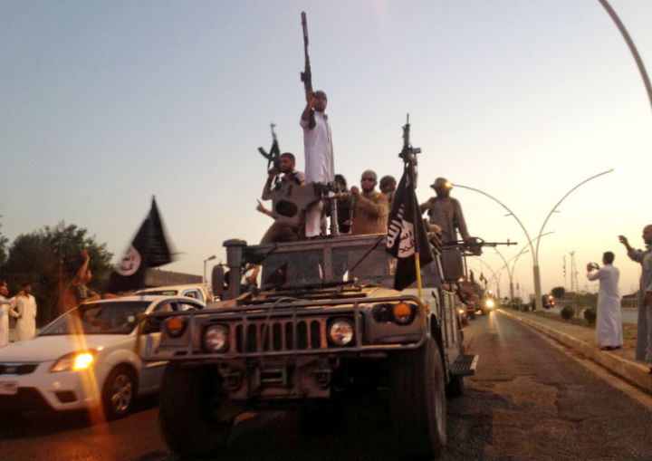 In this photo taken Monday, June 23, fighters from the Islamic State group parade in a commandeered Iraqi security forces armored vehicle down a main road at the northern city of Mosul, Iraq.