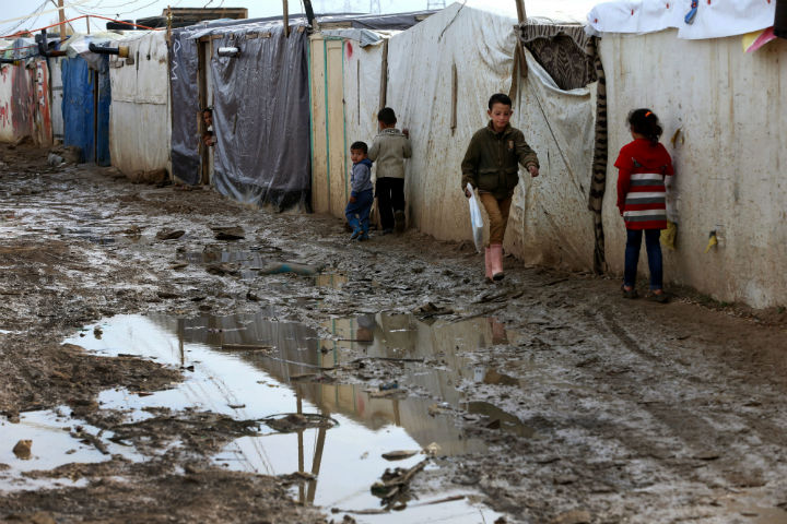 Syrian refugee children walk past tents at a refugee camp in the eastern Lebanese Town of Zahleh, Lebanon, Tuesday, Dec. 2.